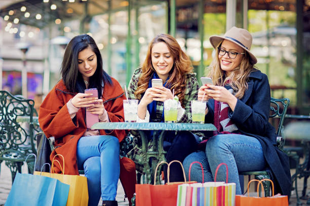 girlfriends are texting in a cafe after shopping - smartphone addiction not groups stock pictures, royalty-free photos & images