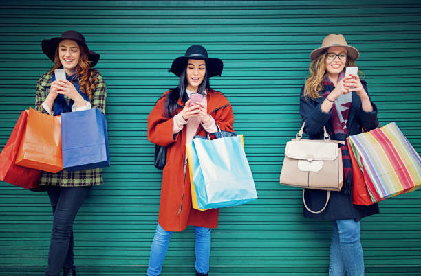 Girlfriends are texting using their mobile phones with a shopping bags stock photo