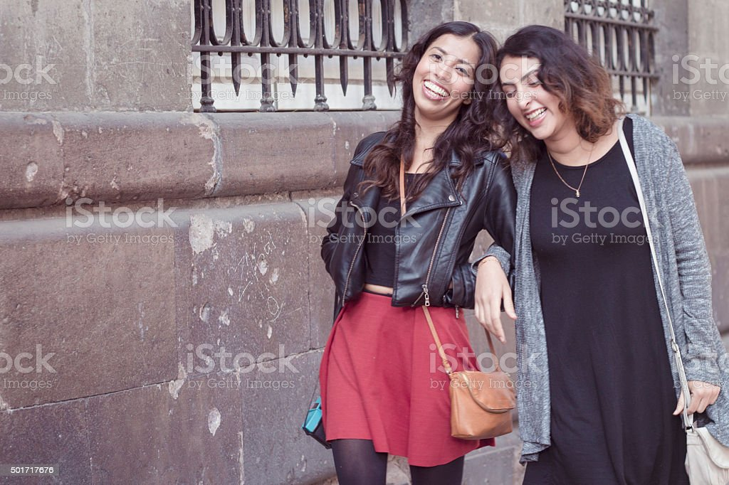 Girlfriends arm in arm laughing taking a stroll stock photo
