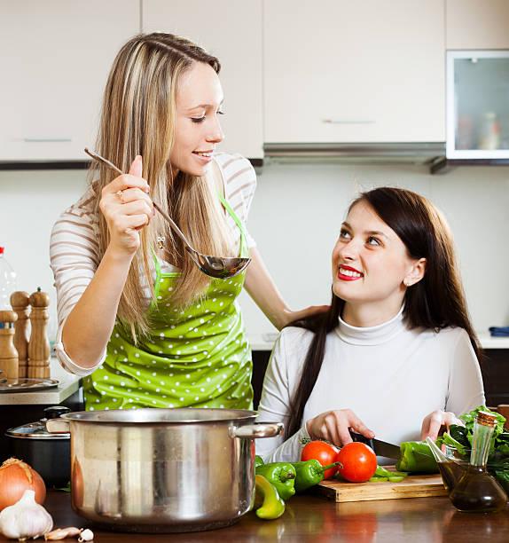 freundinnen kochen mit gemüse etwas - pfannen test stock-fotos und bilder