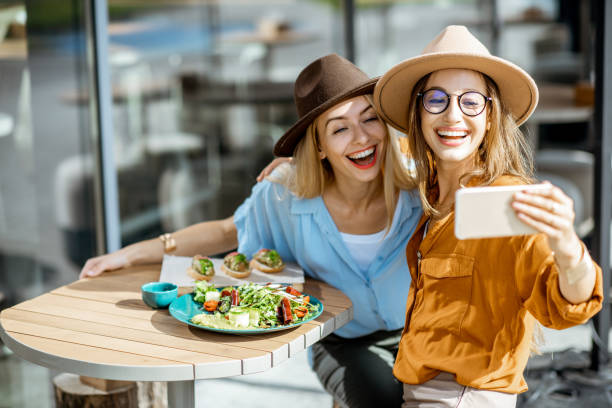 Girlfriends eating healthy food on a terrace stock photo