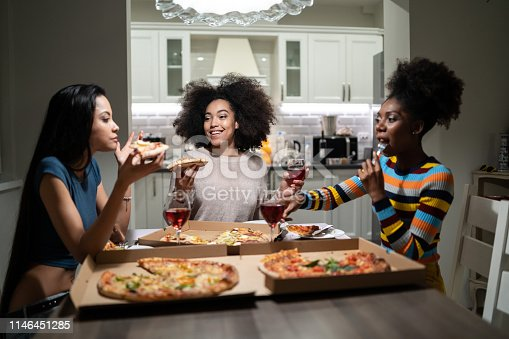 Girlfriends eating pizza and talking at home party