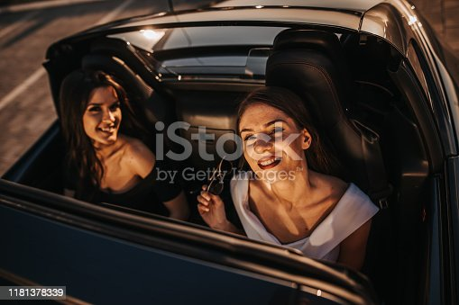 619068028 istock photo Girlfriends having fun on a road trip with open roof cabriolet during sunset 1181378339