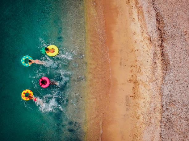 freundinnen spaß am floaties im wasser - urlaub in griechenland stock-fotos und bilder