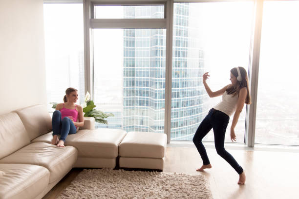 Girlfriends having fun while listening music at home stock photo