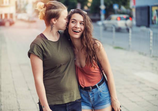 freundinnen umarmen und zusammen auf die straße gehen - hipster unterwäsche stock-fotos und bilder