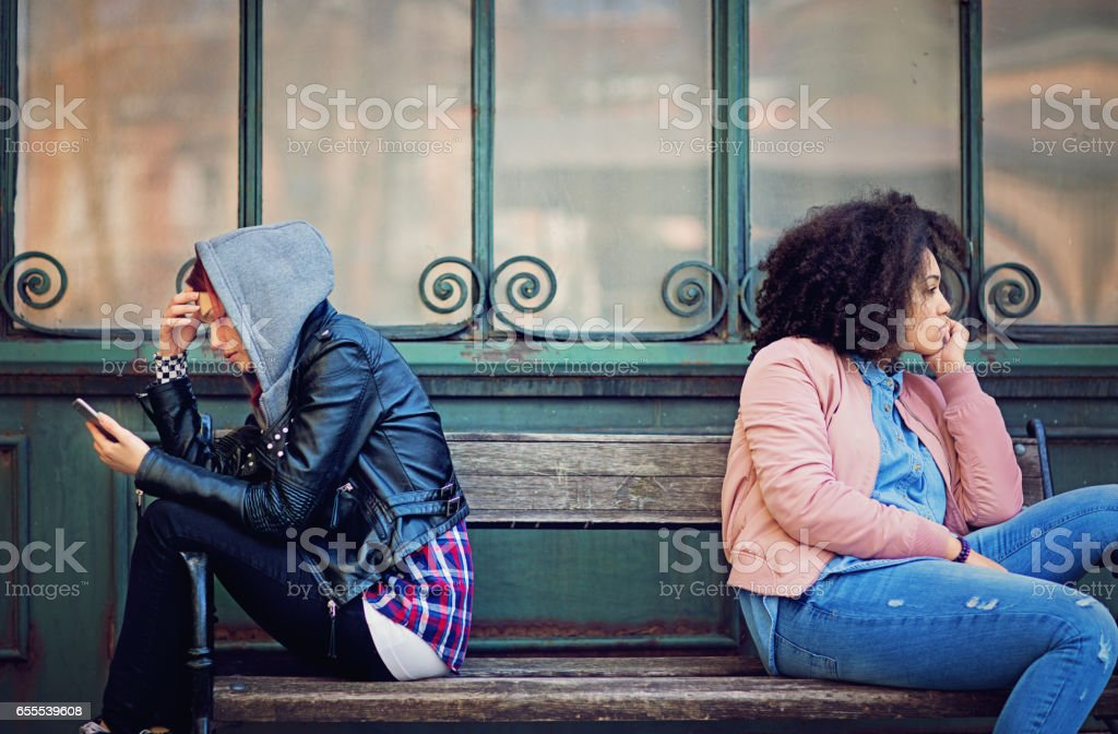 Girlfriends in conflict are sitting on the bench and sulking each other - Photo