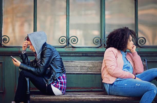 Copines en conflit sont assis sur le banc et bouder les uns les autres - Photo