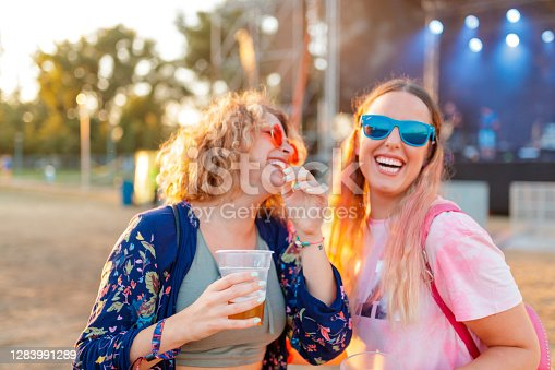 Two young women laughing and having beer and the outdoor music festival, blurred background for generic look