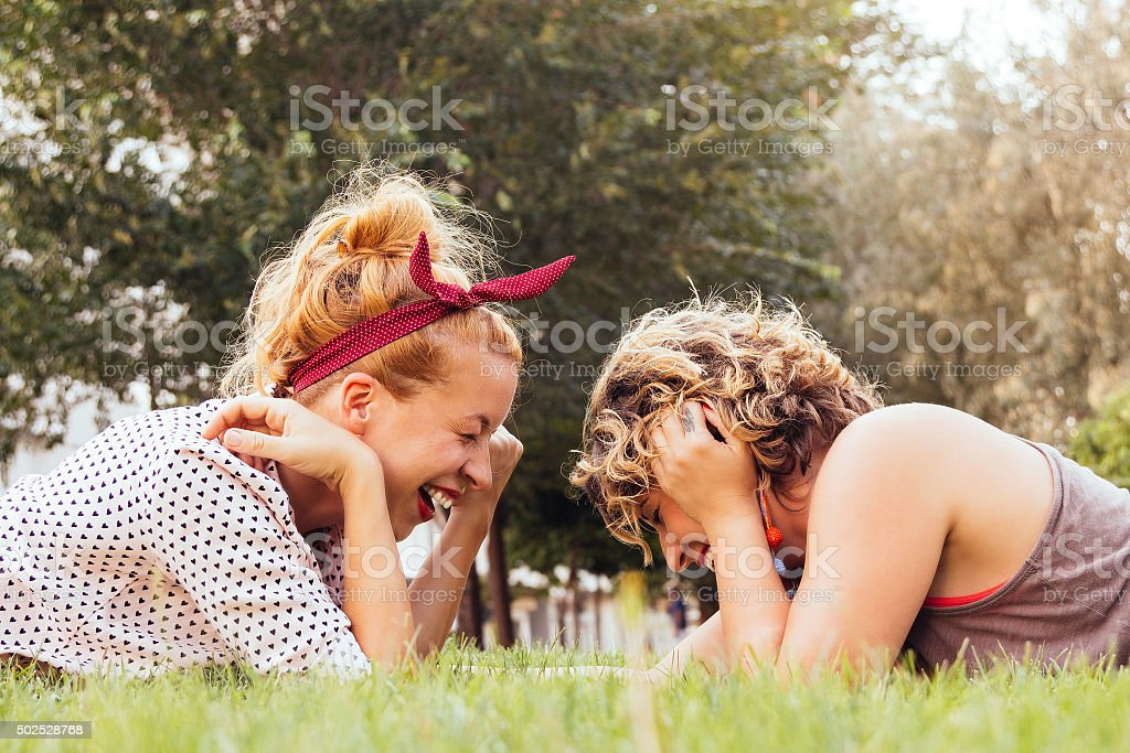 Girlfriends laughing in the park stock photo