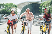 Three beautiful girlfriends making competition with bikes in the big city