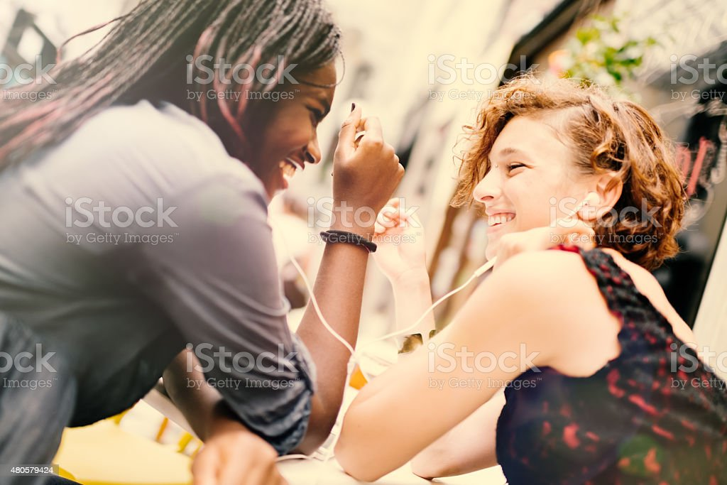 Girlfriends of mixed ethnicity enjoying the time together in sidewalk...