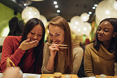 Multi-ethnic group of female friends who enjoy together in each other's company, during dinner in a Japanese restaurant