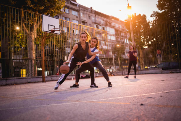 Girlfriends playing basketball Group of females chatting after a leisure basketball game, outdoors. Belgrade, Serbia jump shot stock pictures, royalty-free photos & images