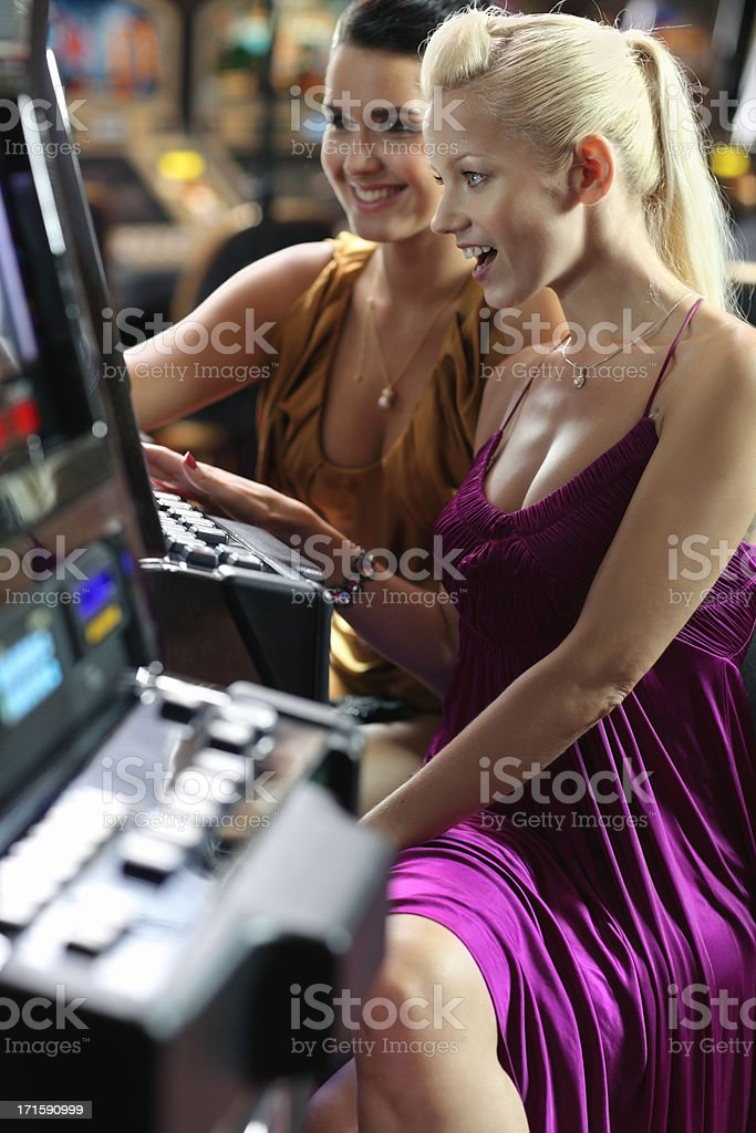 girlfriends  playing on slot machines stock photo
