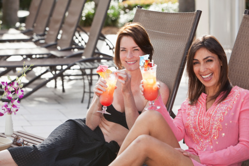 Girlfriends Relaxing By Pool With Drinks Stock Photo