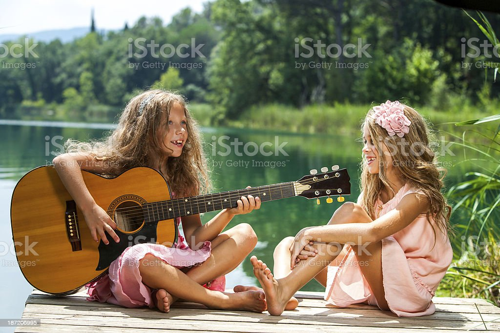 Girlfriends singing together at lake. royalty-free stock photo