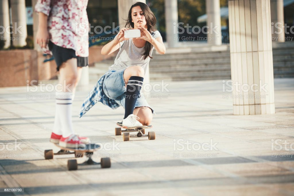 Girlfriends skateboarding and photographing with mobile phone stock photo
