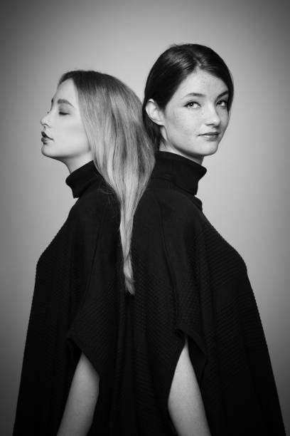 freundin stehen zurück in einen schwarzen sweater - siamesische zwillinge stock-fotos und bilder