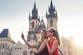 Girlfriends taking selfies in front of Tyn Church in Prague
