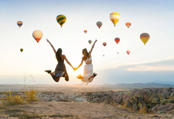 Girlfriends traveling and enjoying valley view at sunset in Cappadocia stock photo