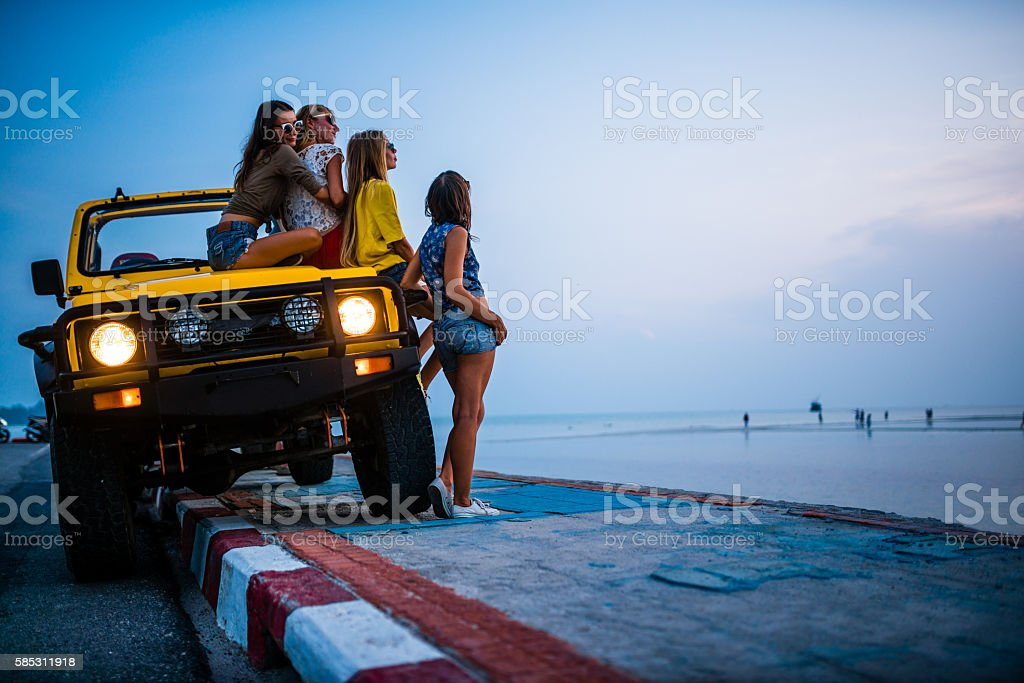 Girlfriends traveling with 4x4 car to the sea stock photo