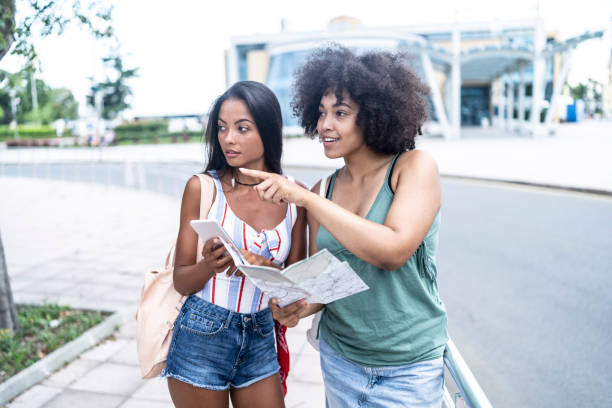 Girlfriends using a map on station stock photo