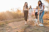 4 Freundinnen genießen den Herbst im Spaziergang mit dem Labrador-Welpen