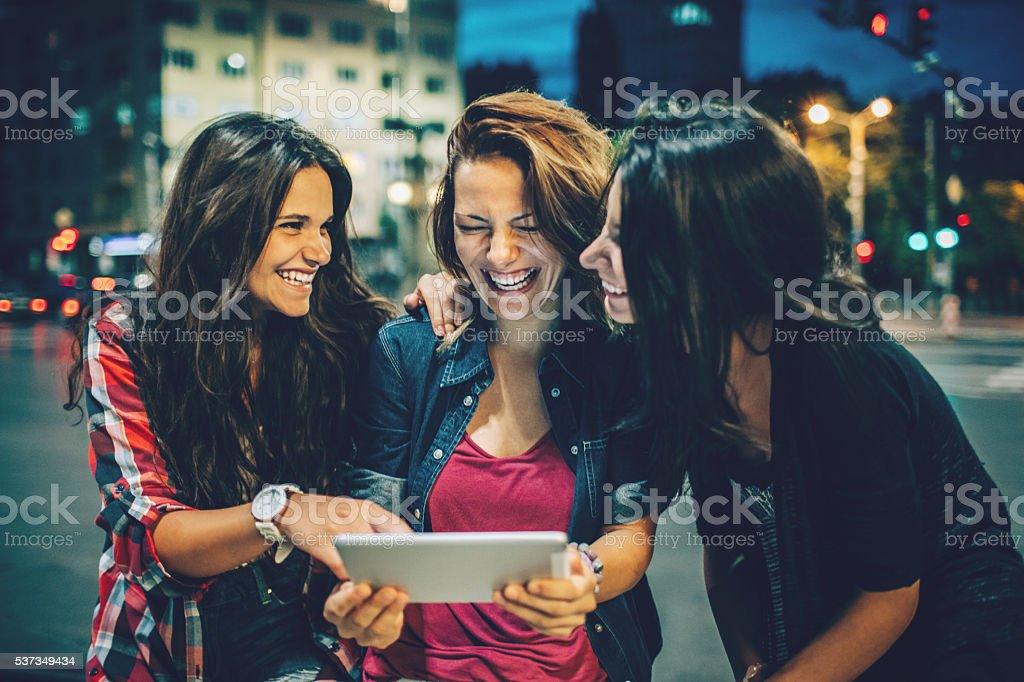 Girlfriends with digital tablet out at night stock photo