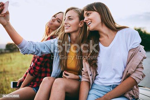 807410214istockphoto Girlriends taking a selfie in a car. 909040888