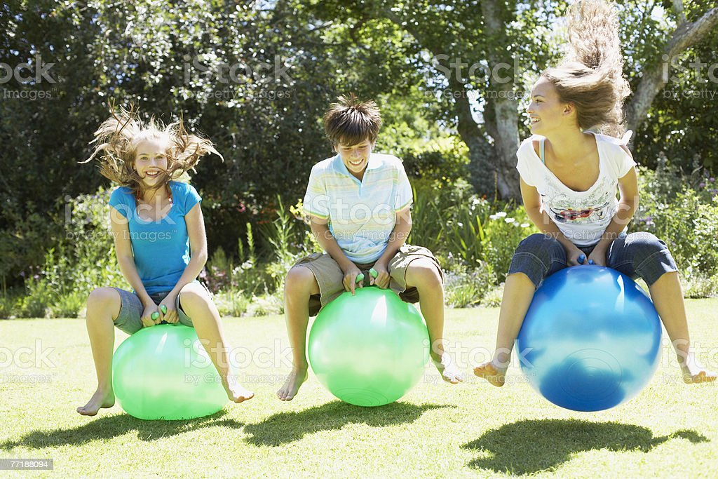 Girls and boy playing on beach balls outdoors royalty-free stock photo