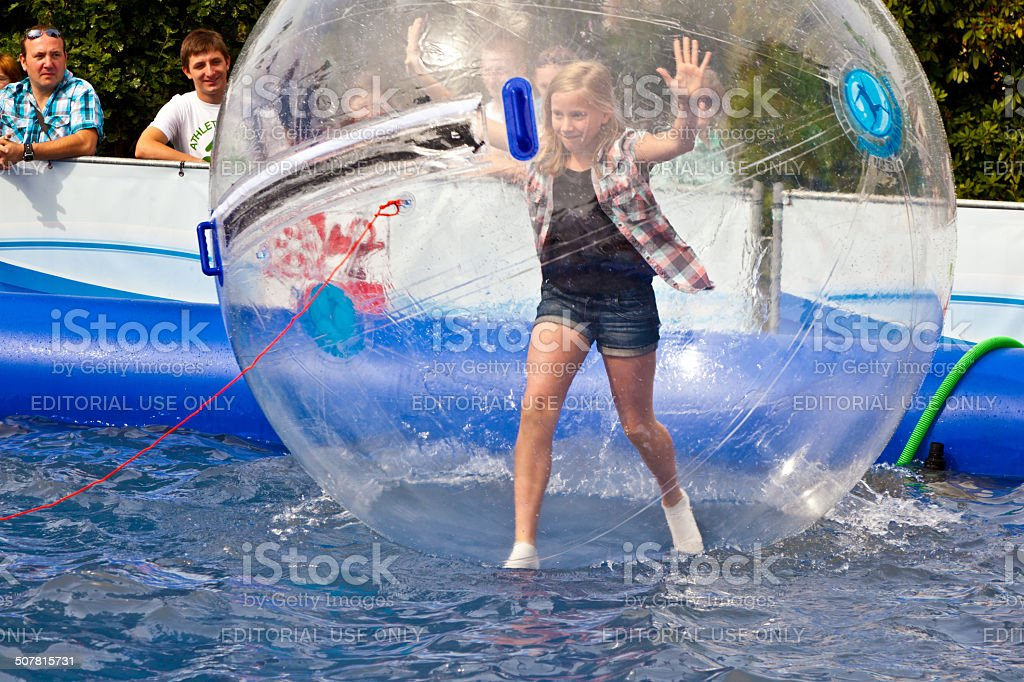 girls and boys have fun in a huge zorbing ball stock photo