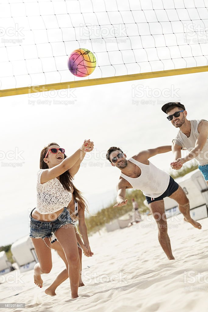 Girls and boys playing beach volleyball in the sun stock photo