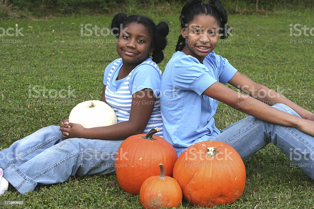 girls and pumpkins stock photo