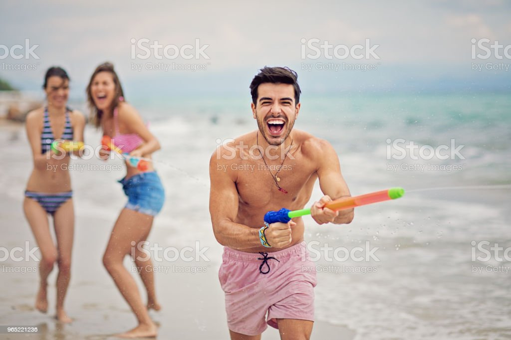 Girls are chasing young man with water guns on the beach and make fun royalty-free stock photo