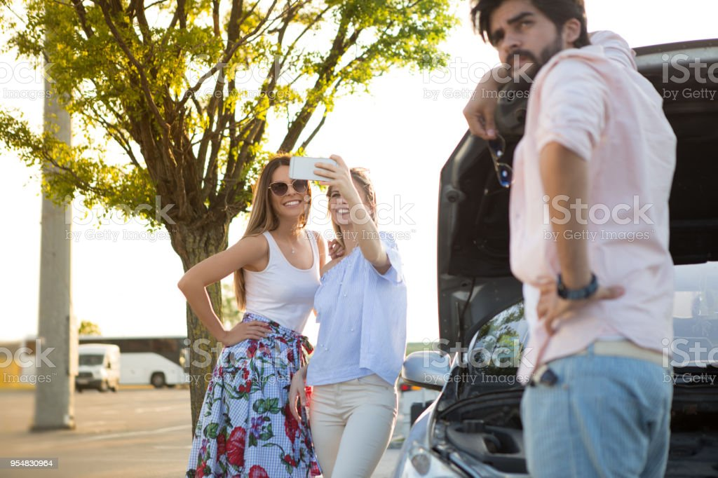 Girls are having fun, even though the car is broken on a journey. stock photo