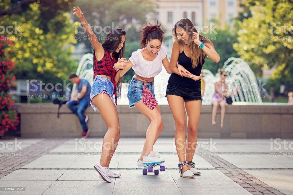 Meninas estão tirando sarro com o skate na frente do chafariz da cidade - foto de acervo