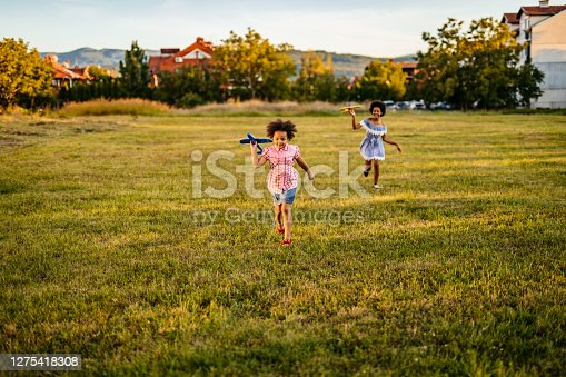 Cute sisters are playing with airplane toys and running in field.
