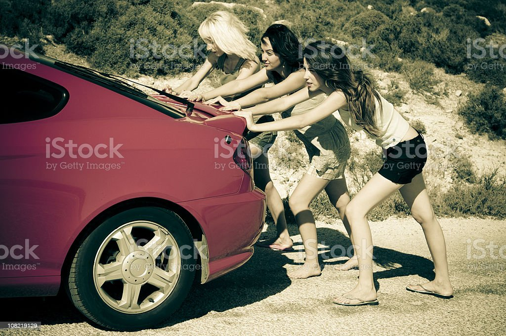 girls are pushing the car royalty-free stock photo