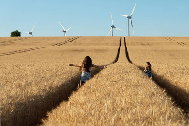 Girls are running the way to wind energy stock photo