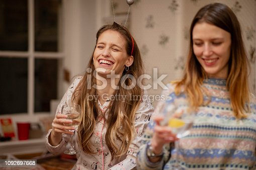 Two young women are laughing and enjoying drinks at a Christmas house party.