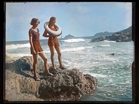 Colourised antique photograph from Edwardian era of two teenage girls at the seaside, one with a Lifebuoy round her neck. circa 1910.