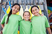Multi-ethnic girls standing in front of canoe paddles at water sports equipment shack.