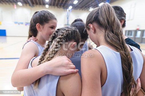 A group of high school girls huddles together with their coach before a basketball game. Their arms are around each other.