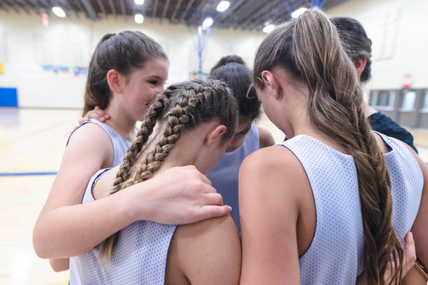 Girls basketball coach leads a pre-game huddle A group of high school girls huddles together with their coach before a basketball game. Their arms are around each other. basketball sport stock pictures, royalty-free photos & images