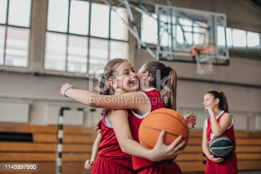 Group of girls, girls basketball players training on court indoors, hug after match