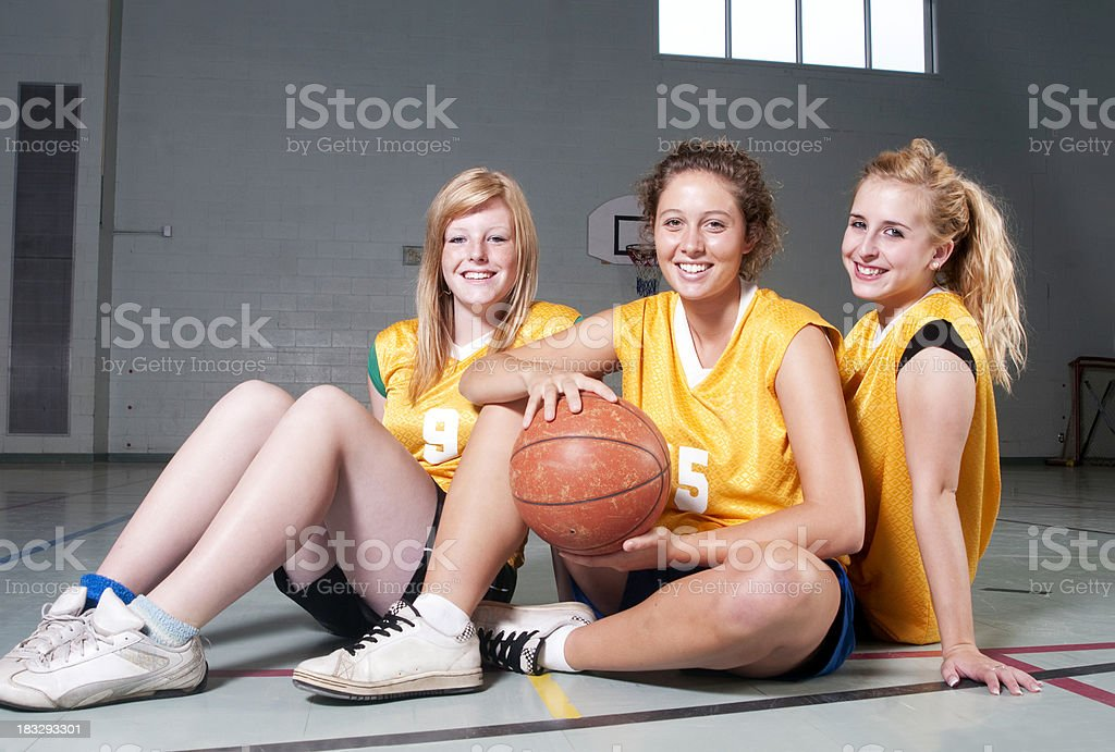 Three girls on their school basketball team hang out after practice.