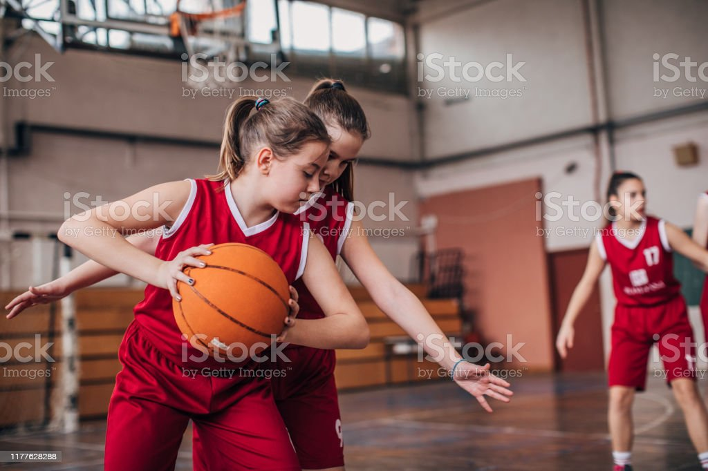 Group of girls, girls basketball players training on court indoors.