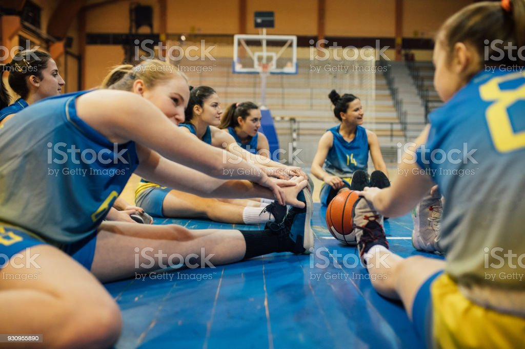 Group of women, stretching on the floor before basketball training.