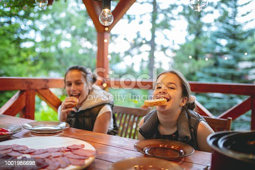 Two girls biting slices of bread cheerfully